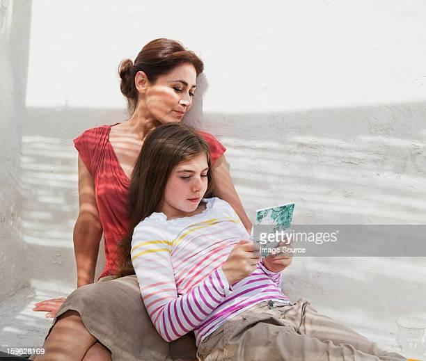 Mother and daughter with hand held device