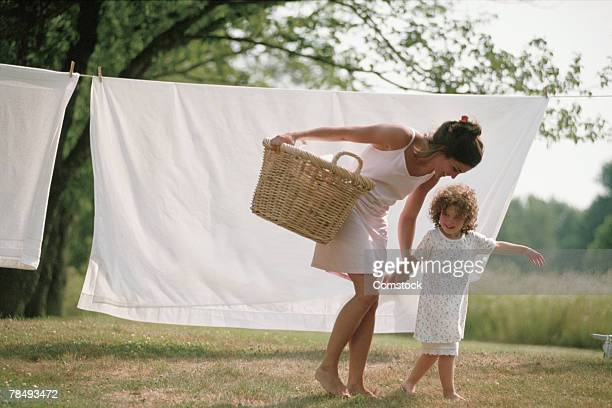 Mother and daughter with laundry on clothesline