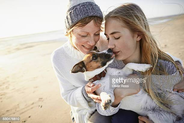 Mother and daughter with little dog on the beach