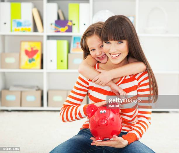 Mutter und Tochter mit Sparschwein.