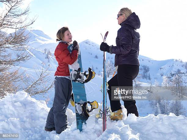 mother and daughter with skis/board talking, slope - バルドネキア ストックフォトと画像