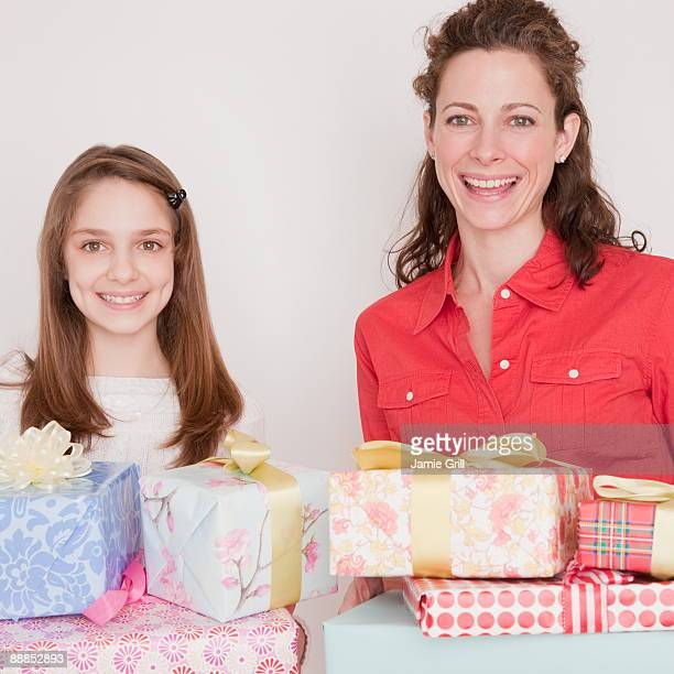 Mother and daughter (10-11 years) with stack of presents, smiling, portrait