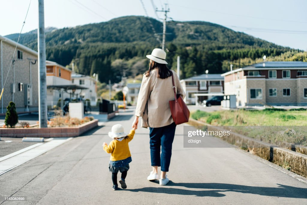 Mother and daughter with straw hat holding hands walking along town in the countryside on a sunny day : ストックフォト
