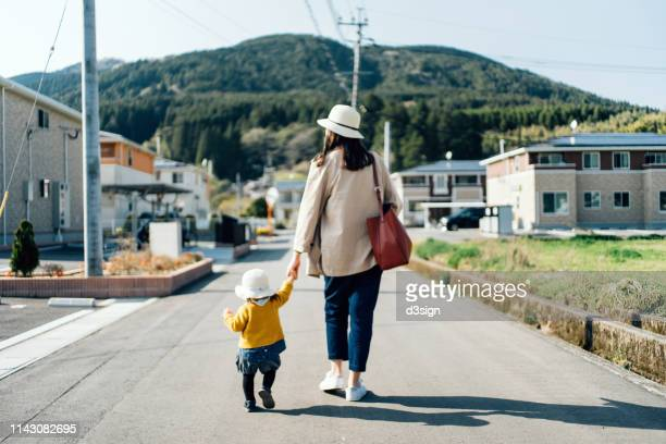 mother and daughter with straw hat holding hands walking along town in the countryside on a sunny day - non urban scene stock pictures, royalty-free photos & images