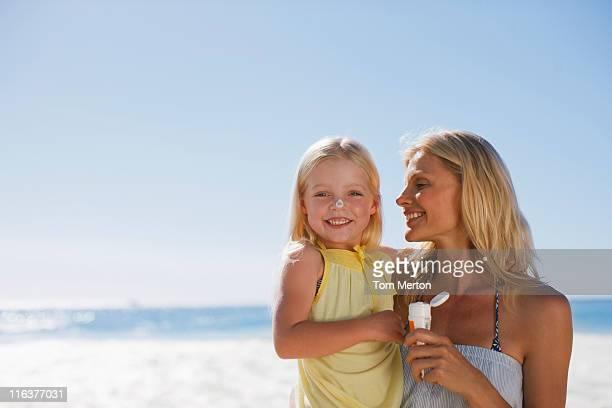 Mutter und Tochter mit Sonnencreme am Strand