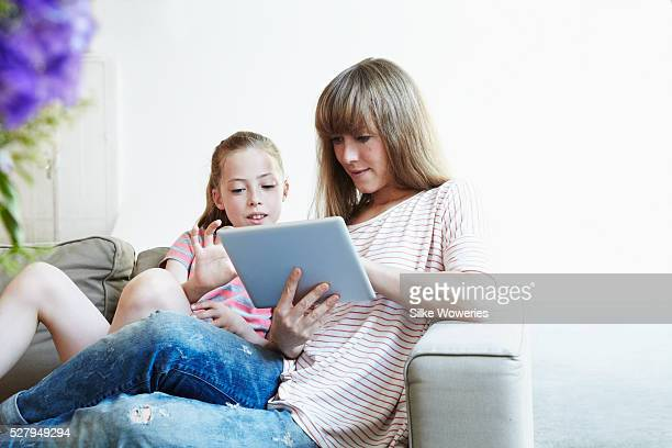 mother and daughter with tablet PC on sofa at home