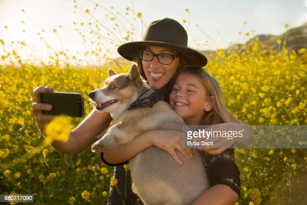 Mother and daughter with their corgi taking a selfie