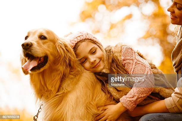 mother and daughter with their dog in autumn park - golden retriever stock pictures, royalty-free photos & images