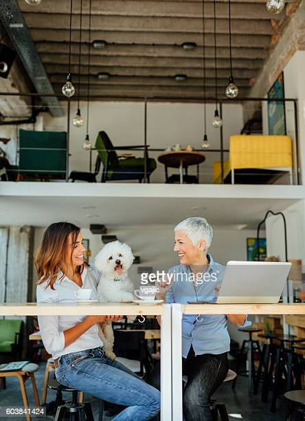 Mother and Daughter With Their Dog In Cafe
