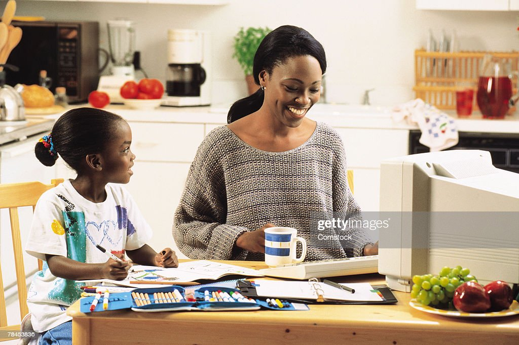 Mother and daughter working at kitchen table : Stockfoto