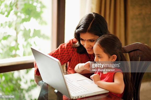mother and daughter working at laptop (horizontal)