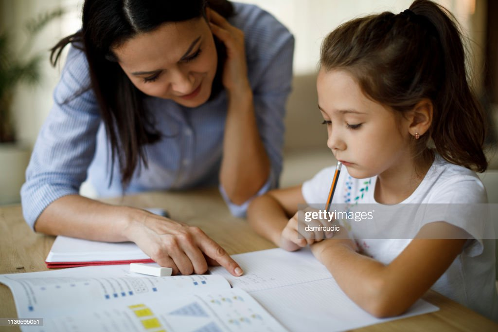 Mother and daughter working homework together : Stock Photo