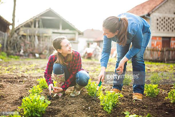 Mother and daughter working in garden