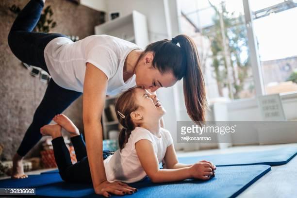 mère et descendant travaillant ensemble faisant l'exercice à la maison - s'entraîner photos et images de collection