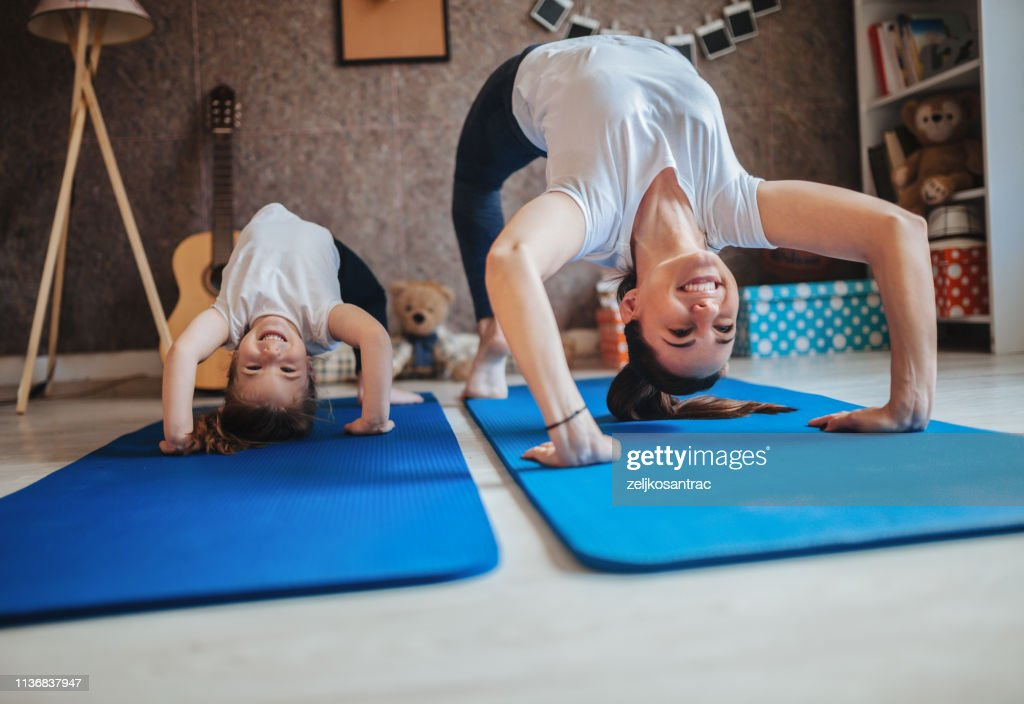 Mother and daughter working out together doing exercise at home : Foto de stock