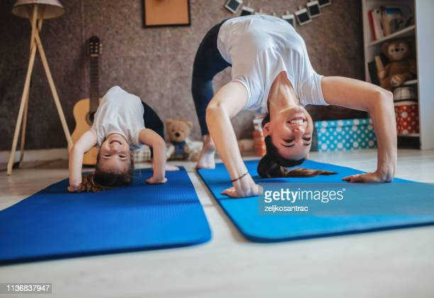 mother and daughter working out together doing exercise at home - exercising stock pictures, royalty-free photos & images