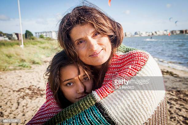 Mother and daughter wrapped in a blanket at beach