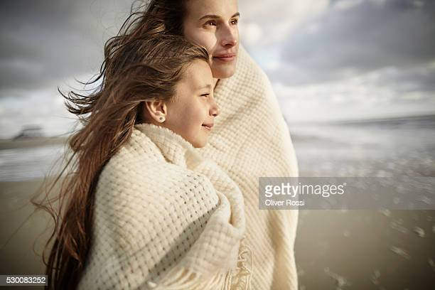 Mother and daughter wrapped in a shawl at the sea