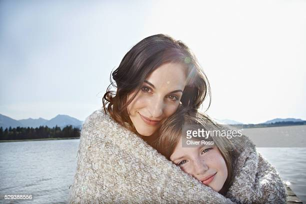 Mother and daughter wrapped in blanket