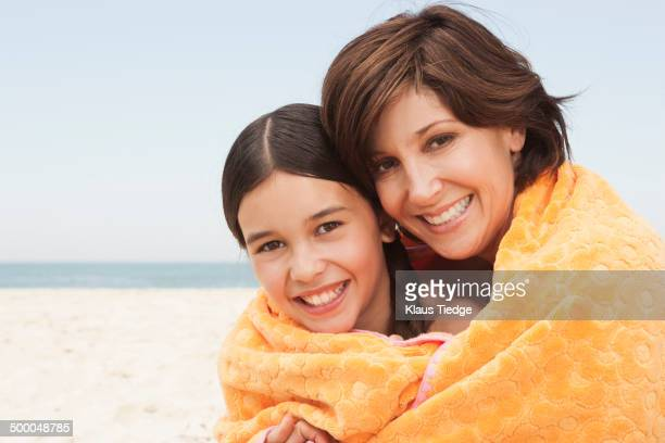 Mother and daughter wrapped in towel on beach