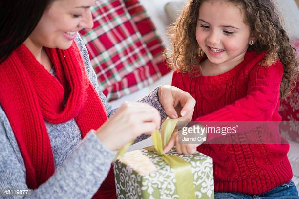 Mother and daughter wrapping present together