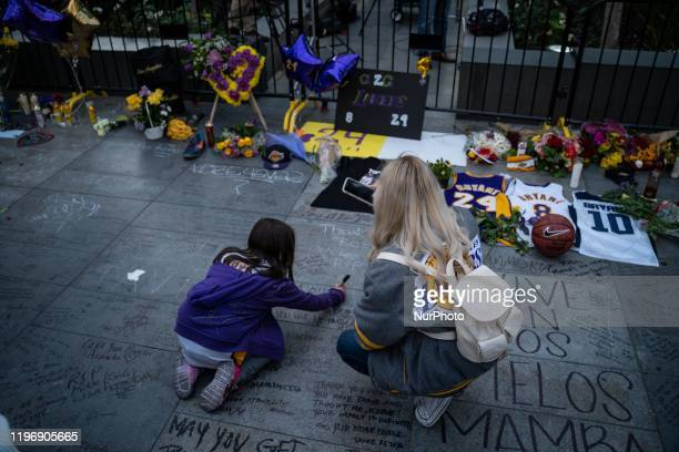 Mother and daughter write a message on the sidewalk for Kobe Bryant and his daughter