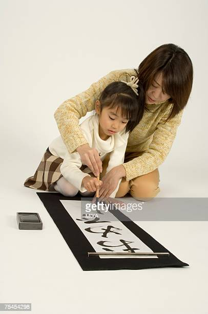 Mother and daughter writing letters with ink brush