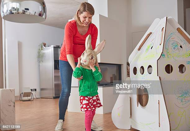 Mother and daughternwith bunny mask at cardboard rocket