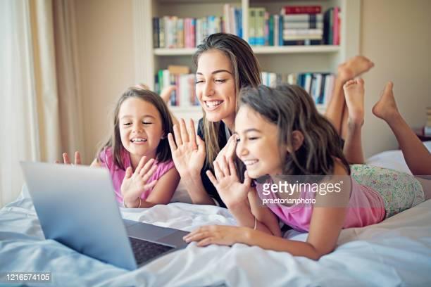 mutter und töchter machen videoanruf / surfen im netz im bett - mother daughter webcam stock-fotos und bilder