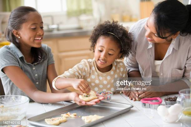 Mother and daughters baking cookies in kitchen