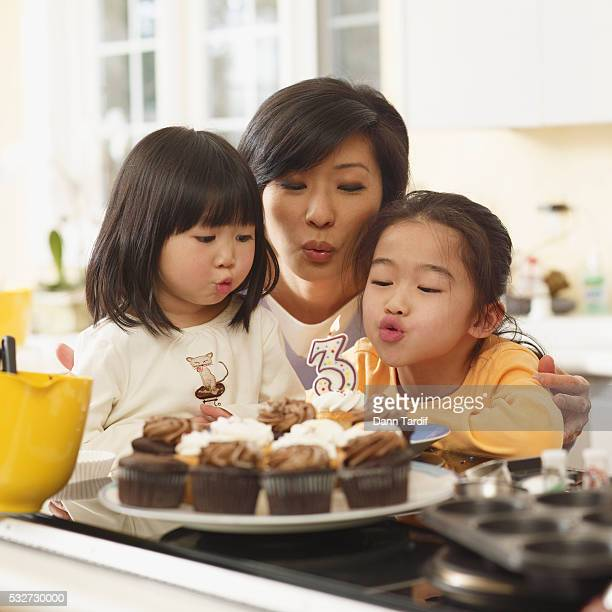 Mother and Daughters Blowing Out Birthday Candle