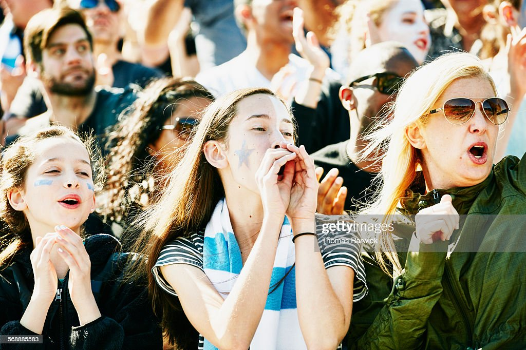 Mother and daughters cheering during soccer match : Stock Photo