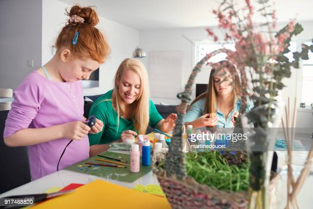 "mother and daughters crafting easter decorations at home. - ""martine doucet"" or martinedoucet stock pictures, royalty-free photos & images"