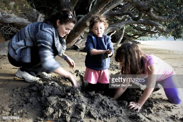 Mother and daughters digging a hole