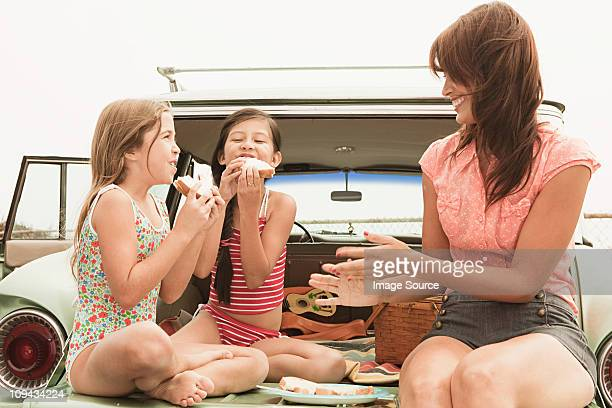 mother and daughters eating sandwiches on car boot - picknick stockfoto's en -beelden
