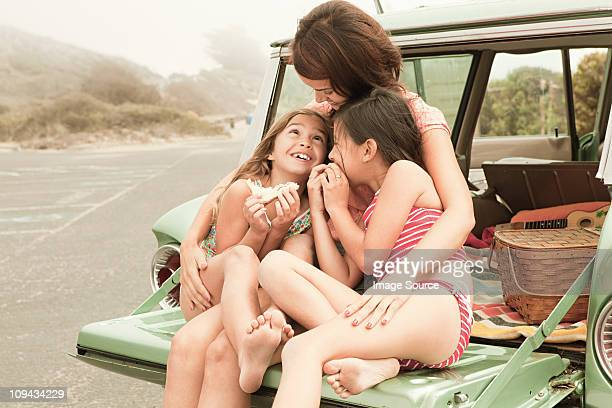 mother and daughters eating sandwiches on car boot - family with two children stock photos and pictures