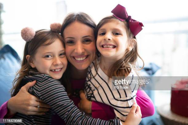 mother and daughters embracing and having fun together at home - single mother stock pictures, royalty-free photos & images