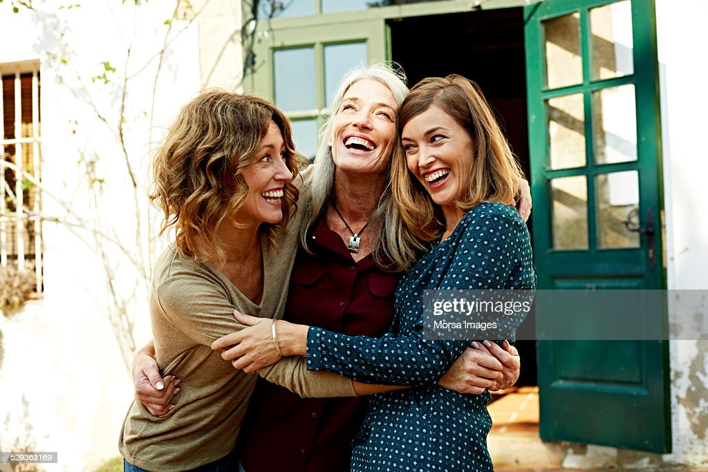 Mother and daughters embracing outdoors : Stock Photo