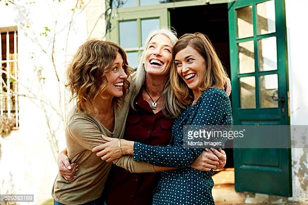 mother and daughters embracing outdoors - lachen stockfoto's en -beelden