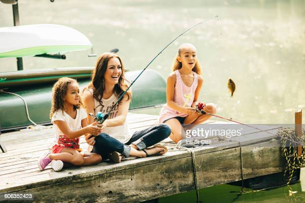 Mother and daughters fishing in lake