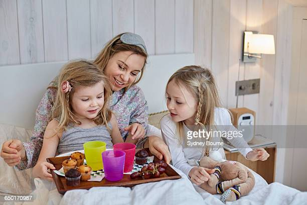 Mother and daughters having breakfast in bed