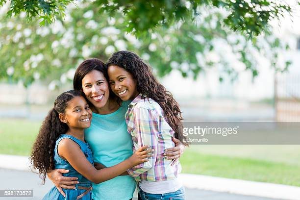 Mother and daughters hugging tightly and smiling at camera