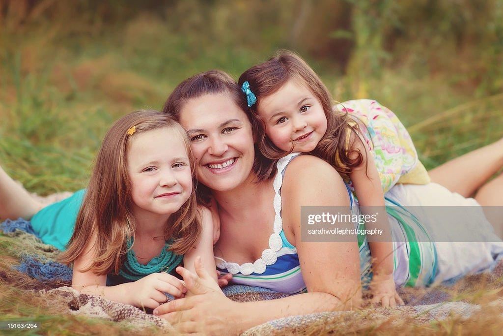 Mother and daughters in grass : Bildbanksbilder