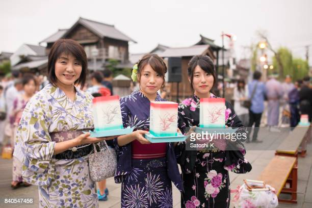 mother and daughters in yukata holding toro nagashi paper products - kanto region stock photos and pictures