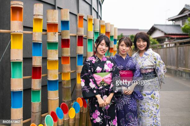 mother and daughters in yukata standing by bamboo lighting - kanto region stock photos and pictures