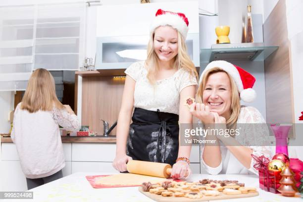 Mother and daughters int the kitchen, baking xmas cookies