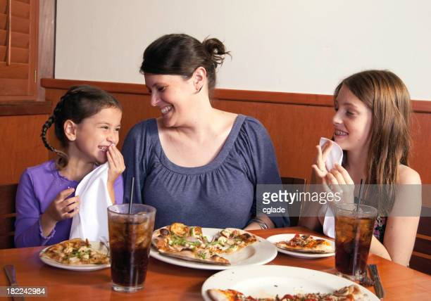 Mother and daughters laughing together while eating pizza