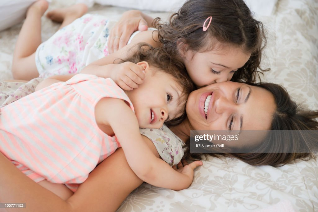 Mother and daughters laying on bed : Stock Photo