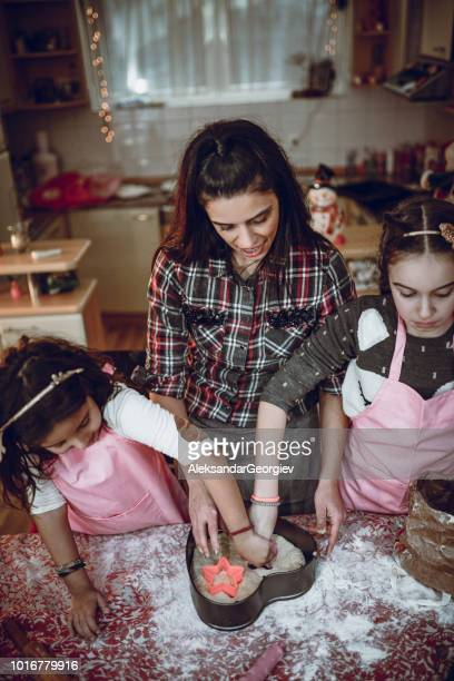 Mother And Daughters Making Cake In Pastry Cutter