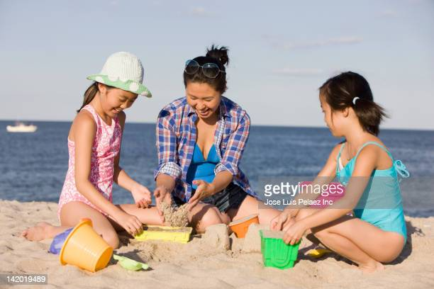 Mother and daughters making sand castle on beach
